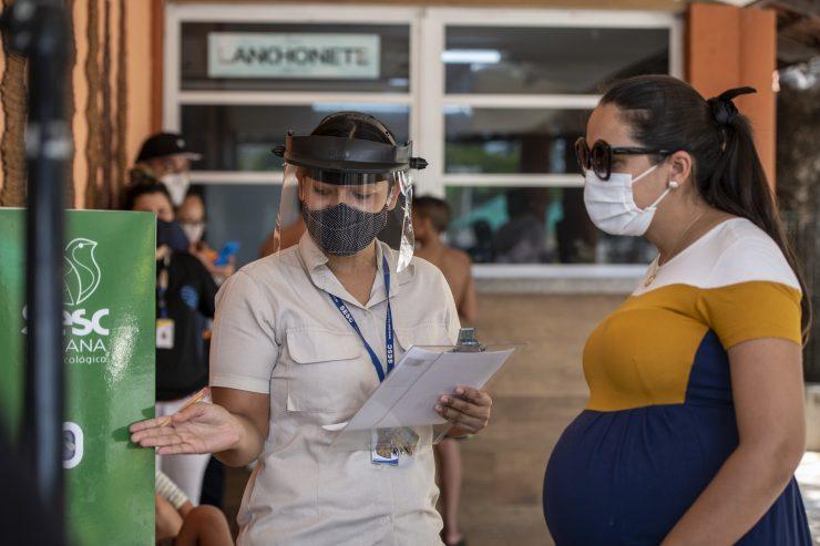 Mulher com face shield na porta do Sesc Iparana, mostrando para mulher de máscara garantia do selo de segurança