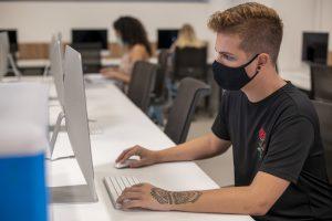 Cursos online: na imagem, em primeiro plano, há um jovem com camisa e máscara pretas digitando em um computador branco. Ele tem uma tatuagem no braço esquerdo e cabelo claro. Atrás, em segundo plano, há mais cadeiras e uma aluna.
