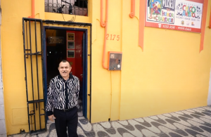 Na imagem, um homem está em frente ao Museu do Humor Cearense, um imóvel amarelo e laranja com detalhes pretos.