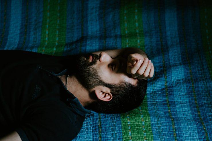 Homem com dor de cabeça, que é um dos sinais de desequilíbrio emocional; confira dicas para ter saúde mental no trabalho