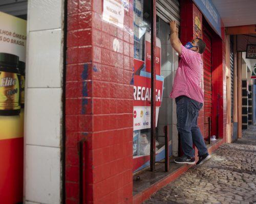 Lockdown: a imagem mostra uma loja de paredes vermelhas sendo fechada por um homem de máscara. Ele usa camisa de cor rosa, calça jeans e tênis.