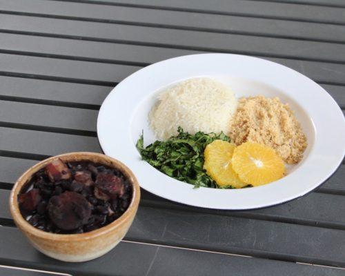 Delivery Café Senac: na imagem, há dois pratos: uma cumbuca com feijoada e um prato branco fundo com arroz, farofa, couve e rodelas de laranja. Os pratos estão em cima de uma mesa de madeira escura.