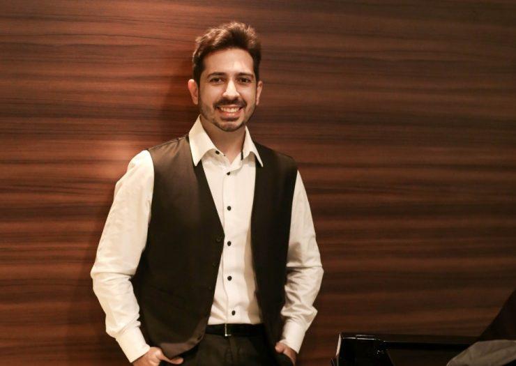 Dia da Mulher: pianista Felipe Adjafre posa ao lado de um piano. Ele usa uma camisa social branca, calça e colete pretos e sorri para a câmera.