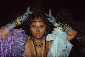 Programação online Fecomércio: na imagem, a cantora Luiza Nobel olha para a foto com as mãos próximas à cabeça. Ela tem a pele negra e o cabelo preto com tranças, está com uma maquiagem artística, luvas azuis e um vestido azul com violeta.