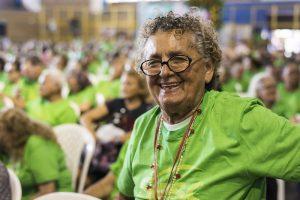 Envelhecimento ativo: na imagem, uma mulher idosa sorri para a câmera. Ela usa camisa verde, óculos com armação preta e cabelos encaracolados e grisalhos curtos.