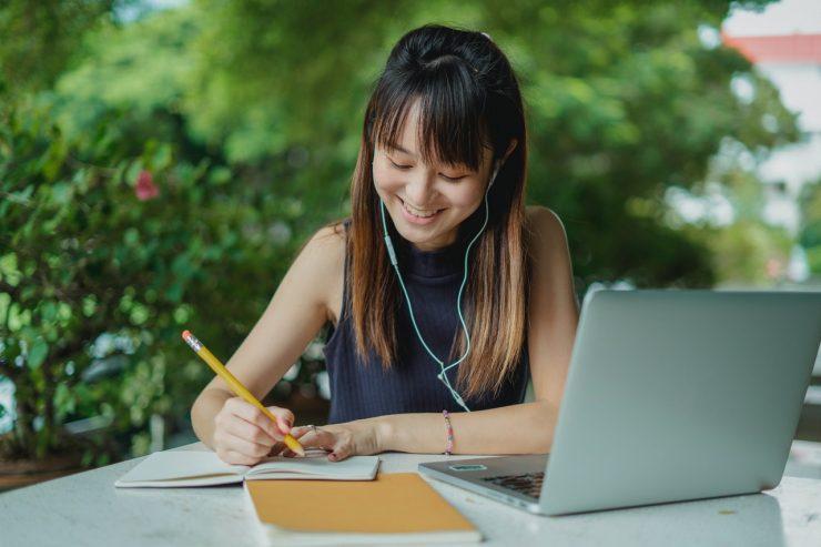 Mulher com bloco de notas e notebook, em curso online