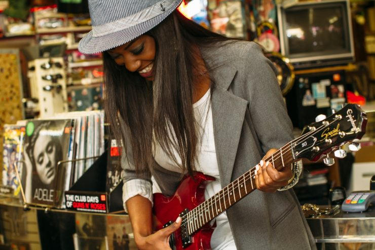 Mulher negra tocando guitarra; Sesc media parcerias culturais