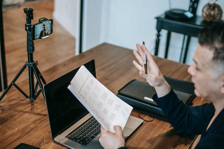 Educação: na imagem, um homem olha para um papel em branco enquanto é gravado em um celular. O celular está em um tripé de mesa. Na frente do homem, há um notebook.