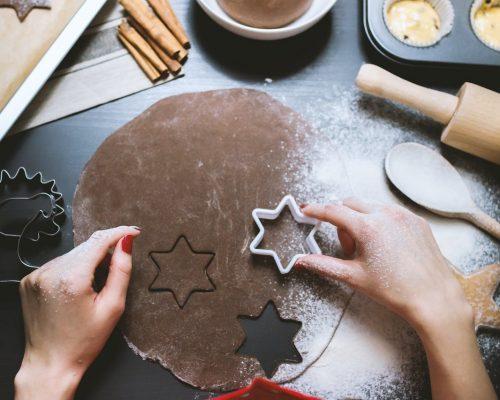 Páscoa: na imagem, um par de mãos femininos utiliza forminhas de bolo em formato de estrela em cima de uma massa de chocolate