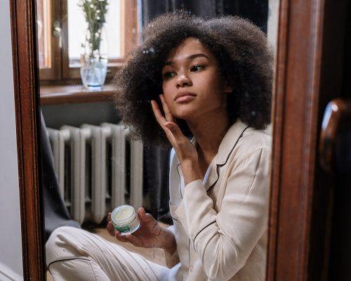Autocuidado: na imagem, uma mulher jovem se olha no espelho enquanto passa um creme branco na face. Ela é negra, tem cabelos crespos e pretos na altura do ombro e usa um pijama de cor clara.