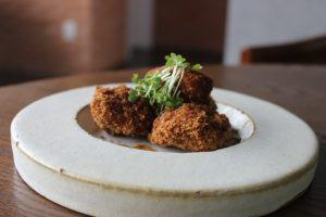 Mayú: na imagem há um prato branco fundo com três bolinhos de carne.