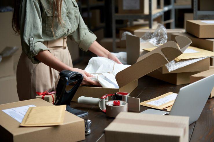 Vendas online: na imagem, uma mulher organiza caixas com produtos em uma mesa. Ela usa camisa verde de manga comprida e uma calça bege de cintura alta. Seu rosto não aparece, mas os cabelos castanhos longos sim.