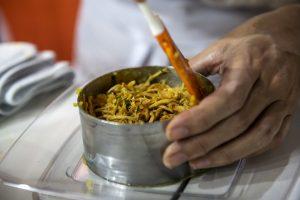 Culinária cearense: a imagem mostra uma mão segurando um pequeno pote de inox e mexendo, com uma colher de pau, pedaços trinchados de carne branca.