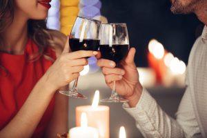 Jantar romântico: na imagem, uma mulher e um homem brindam com taças de vinho em frente a velas acesas.