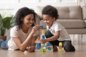 Dia Mundial do Lazer: na imagem, uma mulher jovem brinca de montar blocos com um menino de cerca de 5 anos. Ambos são negros, têm cabelo preto e crespo, usam camisetas de cor clara e estão sorrindo.