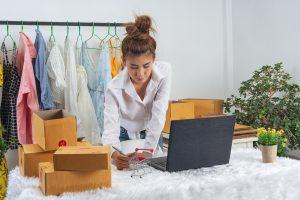 Empreendedorismo: na imagem, uma mulher de camisa social faz anotações em um caderno. Ao lado do caderno, há um notebook aberto. Atrás da mulher, há um cabide com várias peças de roupa.