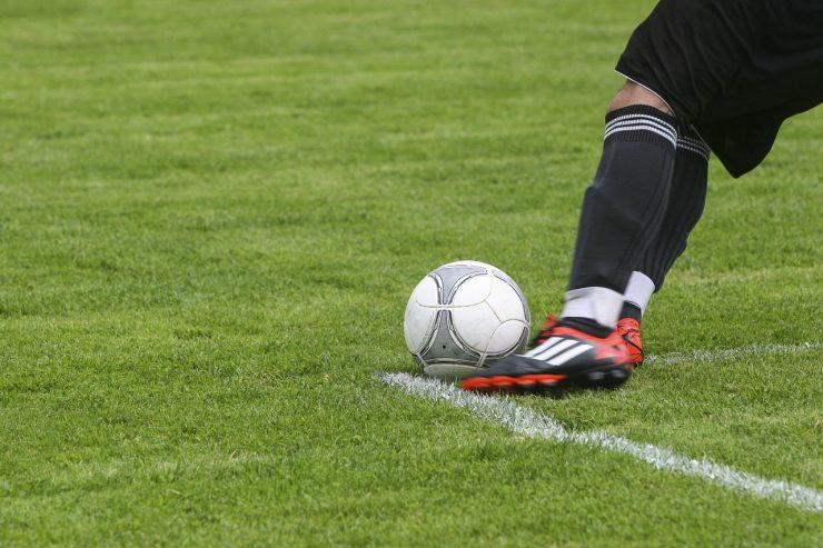perna de um jogador de futebol chutando uma bola em campo