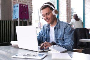 Cursos de licenciatura online: na imagem, um homem jovem acessa um notebook branco enquanto sorri. Ele usa fones de ouvido brancos, camisa branca e jaqueta jeans. Tem pele branca e cabelo curto e claro.