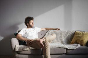 Vitamina D: na imagem, um rapaz jovem de camisa branca está sentado em um sofá de cor clara pegando luz da janela.