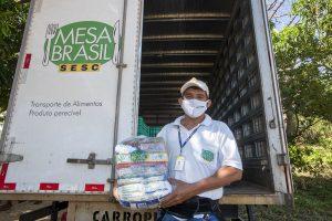 """Mesa Brasil Sesc: na imagem, um homem de máscara, boné e camisa brancos segura uma cesta básica em frente a um caminhão onde se lê """"Mesa Brasil Sesc"""""""