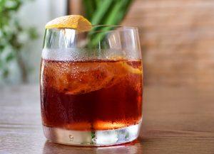 Drinque de Negroni: copo de vidro com líquido laranja, gelo e casca de laranja na borda