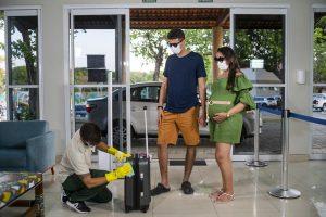 Promoção: homem e mulher grávida chegando a um hotel enquanto funcionário higieniza as malas