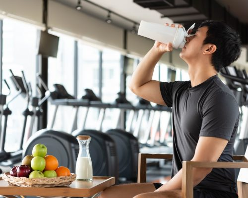Pré-treino: na imagem, um homem jovem e branco bebe em um copo branco e longo. Na frente dele há uma mesa com frutas e leite e, atrás, aparelhos de academia.