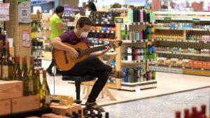 artistas: homem tocando violão em meio a supermercado