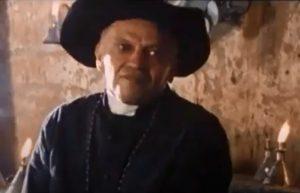 """CineSesc 2021: na imagem, trecho do filme """"Milagre em Juazeiro"""", com um padre de chapéu e batina preta olhando de lado."""