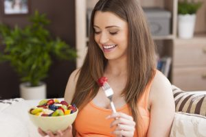 Alimentação saudável: na imahem, uma mulher jovem, branca, de cabelo liso e castanho sorri enquanto segura uma tigela com frutas diversas