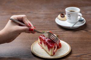 sobremesa: pessoa cortando um pedaço de cheescake de morango com uma xícara de café do lado