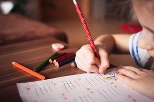 Escola: criança escrevendo em caderno com lapis