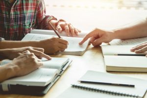 EJA: na imagem, vários pares de mãos escrevem e apontam para folhas de cadernos posicionadas em uma mesa de madeira.