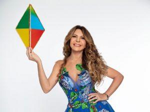 Sesc Junino: na imagem, a cantora Elba Ramanho sorri para a foto em frente a um fundo branco. Ela usa os cabelos loiros cacheados e soltos, segura um balão junino e usa vestido e botas coloridas.