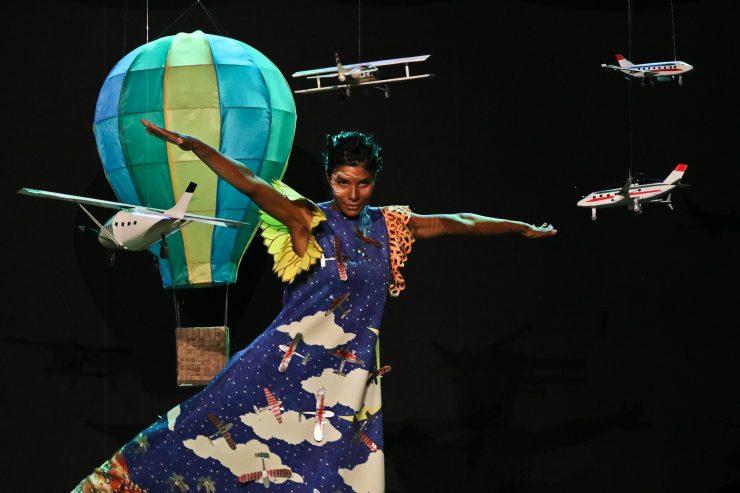 Cariri: a imagem mostra a modelo Suyane Moreira no palco da SPFW. Ela usa um vestido azul com aviões e nuvens e tem os braços abertos, como se quisesse voar. Atrás dela, no cenário, há um balão em tons de verde e vários aviões de brinquedo.