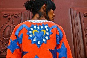 Cariri na moda: a modelo Suyane Moreira está de costas e usa uma das peças da coleção, um casaco laranja vibrante com um coração azul e amarelo bordado no meio. Ela tem cabelo preto e pele parda.