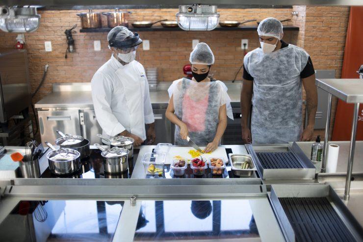 Qualificação profissional: na imagem, uma mulher demonstra técnicas de gastronomia em uma cozinha industrial. Há uma pessoa em cada um de seus lados, e todos estão paramentados com batas, toucas e máscaras de proteção.
