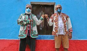Cariri: na imagem, Ronaldo Fraga e Espedito Seleiro se cumprimentam com os punhos e posam para a foto. Ambos trajam vestes com as estampas feitas em couro tradicionais de Espedito, usam óculos e máscaras de proteção. Eles estão em frente a uma casa azul e vermelha.