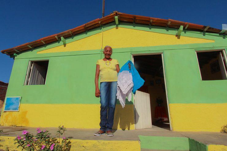 Museus orgânicos: uma mulher idosa vestida de camiseta amarela e jeans posa em frente a uma casa amarela e verde. Ela segura um tecido azul com renda branca e sorri para a foto.
