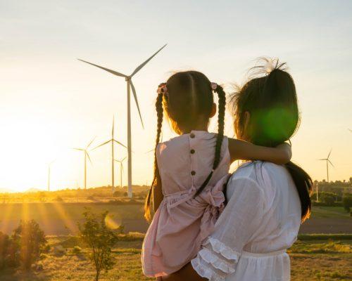 Sustentabilidade: a imagem mostra uma mulher de cabelo preto e camisa branca segurando uma menina também de cabelo preto no colo. A menina usa vestido rosa e duas tranças no alto da cabeça. Ambas estão de costas e contemplando hélices eólicas em um cenário ensolarado.