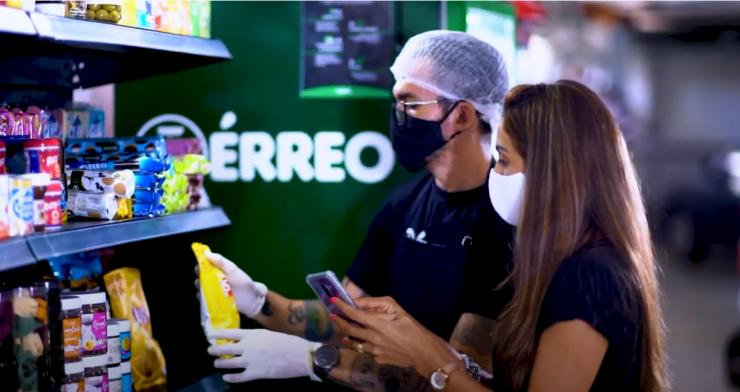 """Empreendedorismo: uma mulher e um homem, ambos de máscaras, olham uma prateleira com vários alimentos. Ele usa touca e luvas descartáveis. Ao fundo, se lê """"Térreo"""" na parede verde."""