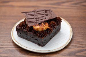 Chocolate: brownie confeitado em um prato branco de sobremesa