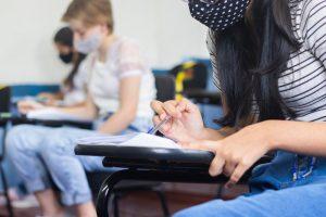 Curso pré-universitário: alunos de máscara, camiseta e calça jeans estão sentados em carteiras fazendo anotações.