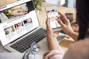 e-commerce: pessoa mexendo em celular com notebook ligado atrás