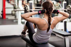 Hábitos saudáveis: uma mulher branca com cabelo castanho em um trança faz um abdominal. Ela está de costas e usa luvas pretas, regata branca e uma legging de ginástica.