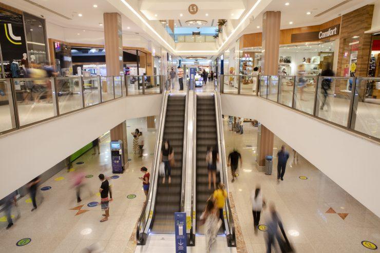 Dia do Comerciante: a imagem mostra a área interna de um shopping, com duas escadas rolantes e muitos clientes andando pelo espaço.