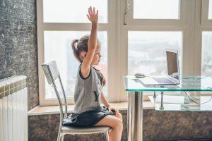 Brincando nas Férias: a imagem mostra uma menina sentada em uma cadeira em frente a um notebook. Ela é branca, usa uma regata cinza e uma saia preta, tem cabelos claros e lisos presos em um rabo de cavalo está com uma das mãos levantadas.
