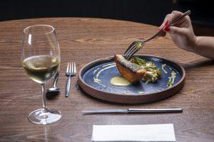 Mayú: uma mão segura um garfo com um pedaço de peixe em um prato de cor escura. Ao lado, há uma taça com vinho branco.