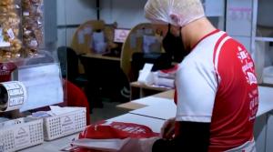 Menu Brands: um homem com máscara de proteção preta, touca descartável e camisa do grupo Menu Brands embala um pedido para delivery.
