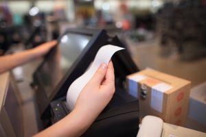 Nota fiscal: foto mostra uma mão branca segurando uma nota fiscal ao lado de uma tela de computador preta.